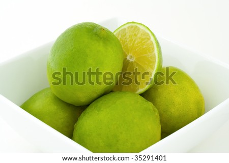 Whole green limes and a half of a lime in white porcelain bowl. Isolated on white background. - stock photo