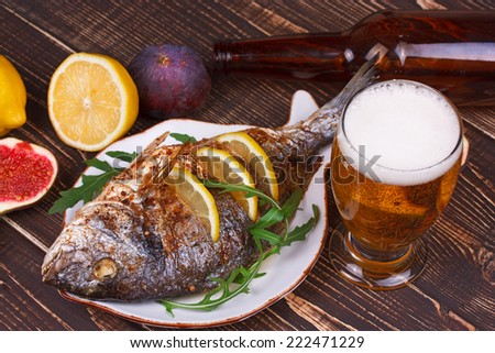 Whole grilled fish dorado served with lemon and figs - stock photo