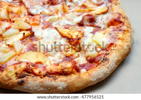 Whole Hawaiian pizza with pineapple and chicken in delivery box