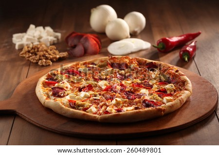 whole italian pizza on wood table with ingredients  - stock photo