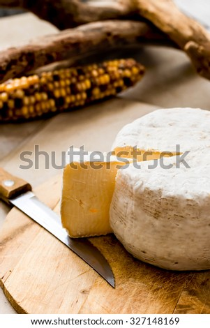whole mature cheese over chopping board and autumnal background