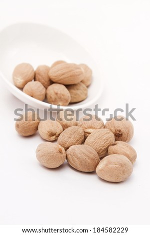 Whole nutmeg in white bowl - stock photo