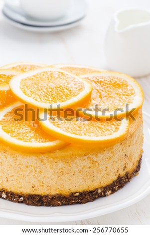 whole orange cheesecake on plate, close-up, vertical - stock photo