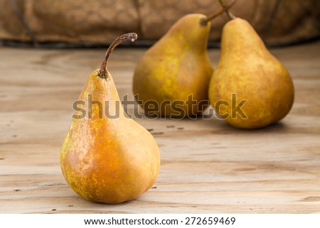 whole pears on wooden background  - stock photo