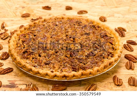 Whole pecan pie with pecans on wooden background. - stock photo