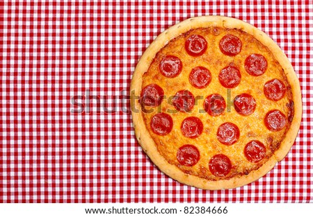 Whole pepperoni pizza on red gingham tablecloth with copy space. - stock photo