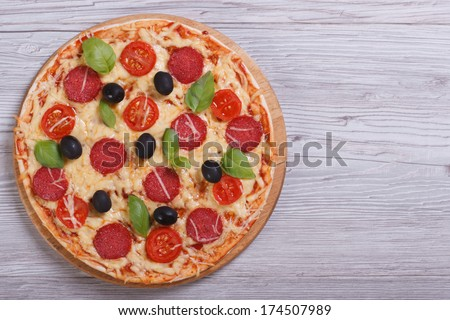 whole pizza with salami, tomato, cheese, olives and basil on the table. top view