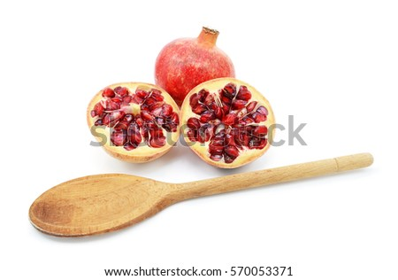 Whole pomegranate with two cut halves, with wooden spoon for removing seeds, isolated on a white background