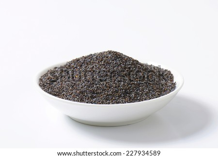Whole poppy seeds on plate - stock photo