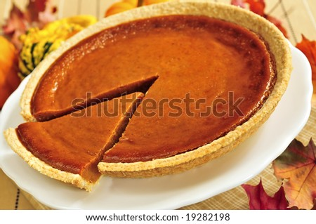 Whole pumpkin pie with a slice cut out - stock photo