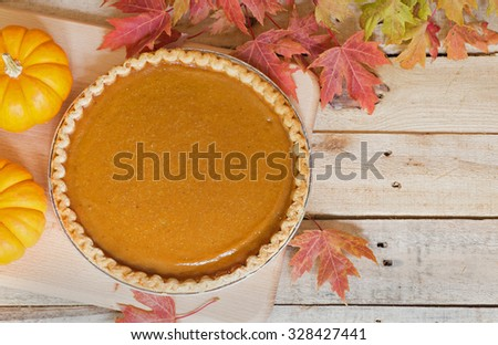 Whole pumpkin pie with colorful fall leaves - stock photo