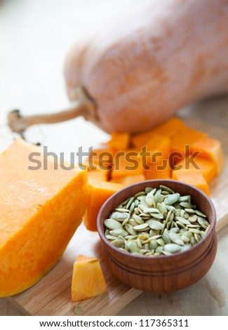 Whole pumpkin, seeds in a bowl and pieces of pumpkin, close up - stock photo
