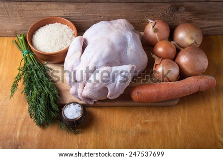 Whole raw chicken, onion, carrot, dill, rice, salt on wooden background. Rustic still life. - stock photo