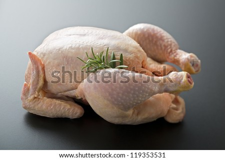 Whole raw chicken with rosemary close up - stock photo