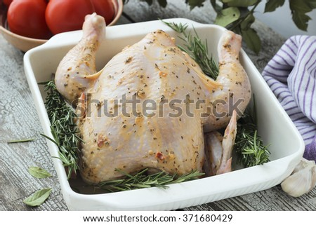 Whole raw chicken with rosemary in ceramic bowl ready for cooking - stock photo