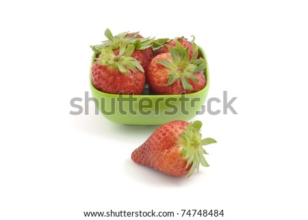 Whole ripe strawberries in square green dish isolated on white background