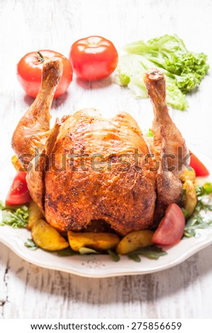 Whole Roasted Chicken on a plate with fried potatoes