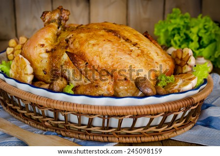 Whole roasted chicken stuffed with buckwheat and mushrooms on wooden table  - stock photo