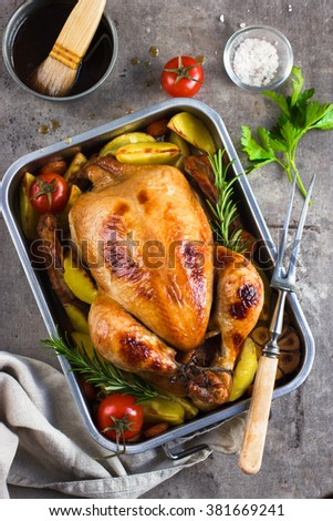 whole roasted chicken with vegetables and herbs, top view - stock photo