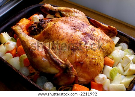 Whole roasted chicken with vegetables in the roasting pan. - stock photo