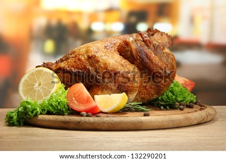Whole roasted chicken with vegetables on plate, on wooden table in cafe - stock photo