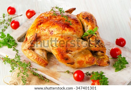 Whole roasted chicken with vegetables on wooden board.