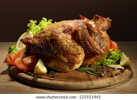 Whole roasted chicken with vegetables, on wooden table, on brown background - stock photo