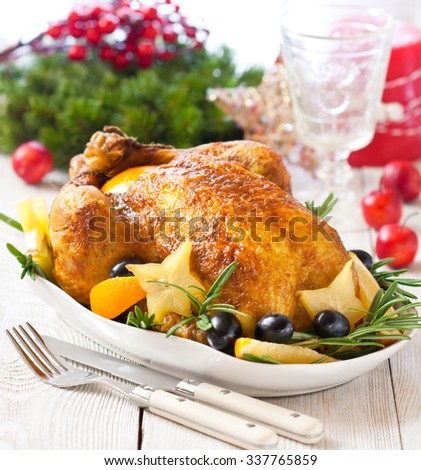 Whole roasted orange chicken with fruit garnish and rosemary for Christmas dinner.