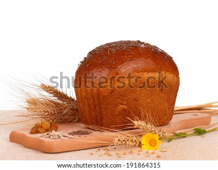 Whole rye bread on a cutting board over white background - stock photo