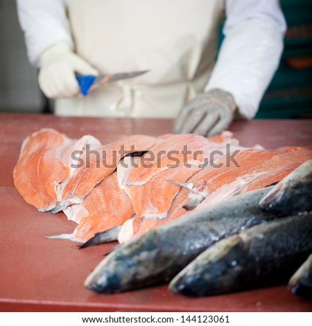 whole salmon and salmon fillets with worker in background