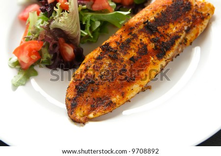 Whole seasoned fillet of white fish on mixed salad with tomato