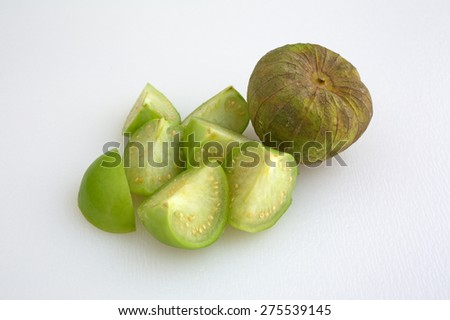 Whole tomatillo with husk and seven green cut sections with seeds. - stock photo