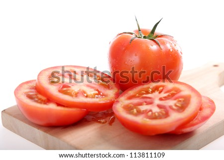 whole tomatoes and tomato slices on a cutting board - stock photo