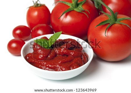 Whole tomatoes with dish of tomato puree, over white background. - stock photo