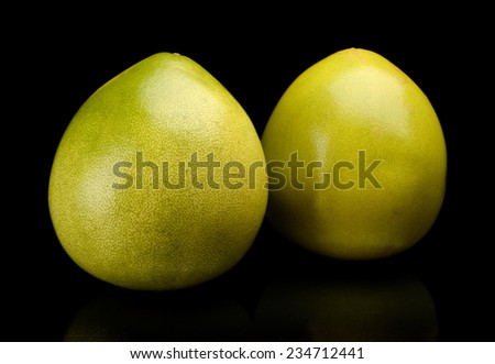 Whole two pomelos, chinese grapefruits isolated on black background - stock photo