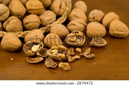 Whole Walnuts in Basket with Whole and Cracked Walnuts on Wood Table - stock photo