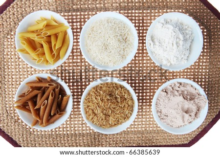 Whole Wheat and Brown Rice Versus White Pasta, Flour and Rice on a Table Mat in  Bowls - stock photo