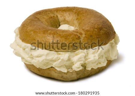 Whole wheat bagel filled with a generous amount of cream cheese - stock photo