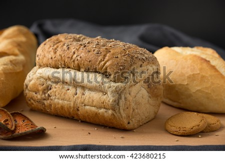 Whole wheat bread and French baguette - stock photo