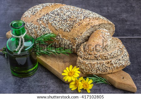 Whole wheat bread and rye, sprinkled with sunflower seeds, poppy seeds, sesame seeds, sliced on the board, next to a jar of olive oil, rosemary and yellow daisies on a dark background - stock photo