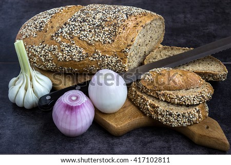 Whole wheat bread and rye, sprinkled with sunflower seeds, poppy seeds, sesame seeds, sliced on the board with a knife next to the onion and garlic - stock photo