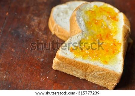 Whole wheat bread, brush with orange marmalade. - stock photo