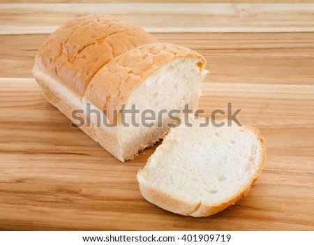 Whole wheat bread loaf on wooden cutting surface. - stock photo