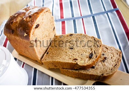 whole wheat bread slided in wooden plate on table with tablecloth, food closeup