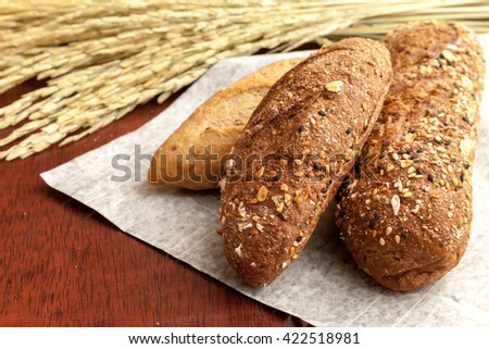 Whole wheat French baguettes and dried rice plants on wooden table - stock photo