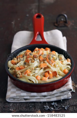 Whole wheat pasta with roasted salmon and cream sauce in a pan - stock photo