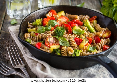 Whole wheat pasta  with vegetables on cast iron pan - stock photo