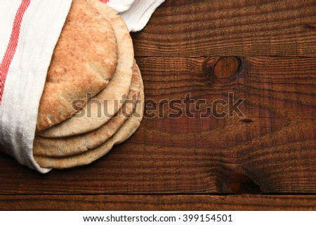 Whole wheat pita bread on a rustic wood table with copt space. The bread is wrapped in a towel and seen from a high angle.