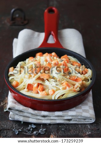 Whole wheat spaghetti or linguine pasta with roasted salmon, cream sauce, dried herbs and pine nuts in a pan - stock photo