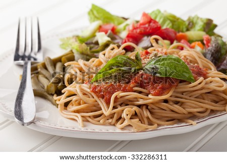 whole wheat spaghetti topped with organic homemade marinara sauce served with green beans and an Italian side salad side view on white wood